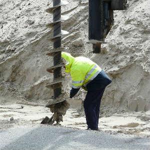 construction worker using an auger